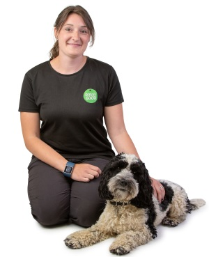 Trainer Jen with cockapoo laying beside her