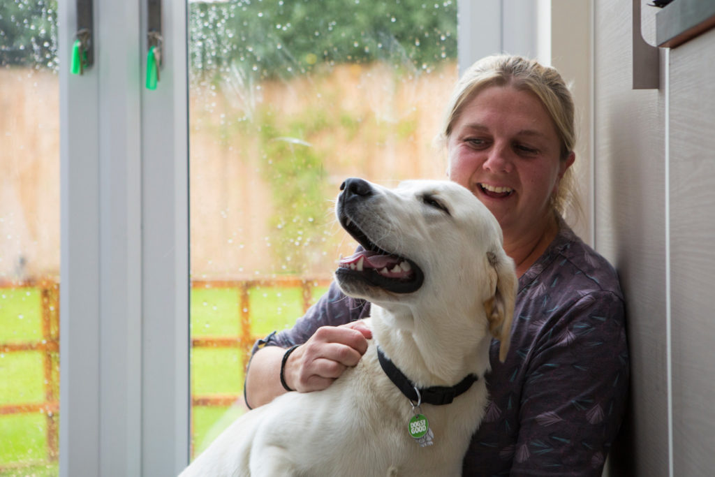 Volunteer at home with young labrador dog