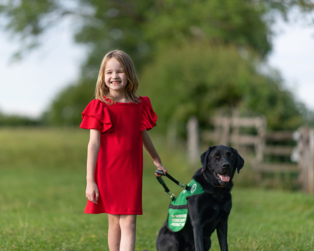 Emily is wearing a red dress and standing next to her autism assistance dog Oslo holding his harness