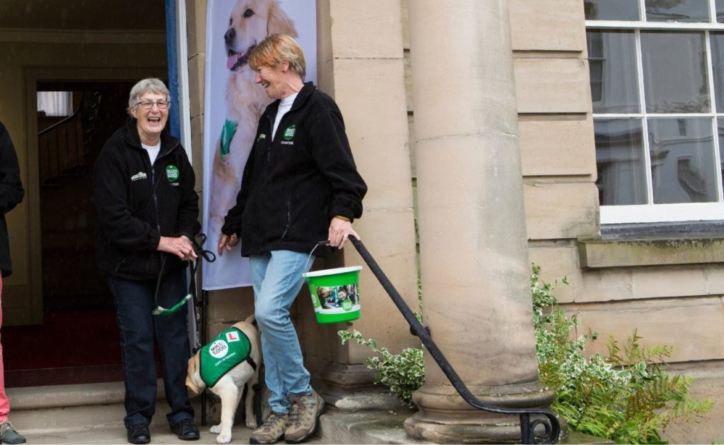 Two members of the Warwickshire supporter group outside an event with a fundraising bucket and an assistance dog