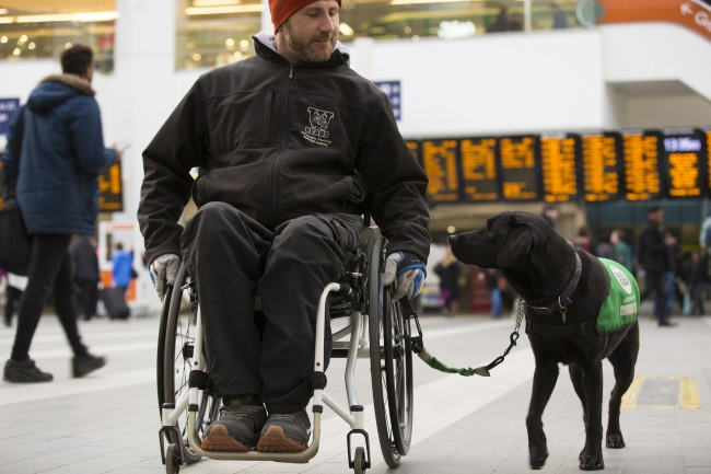 Man in wheelchair with black labrador walking alongside at train station