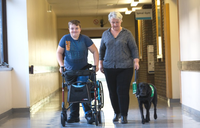 Samuel walking on a frame with assistance dog Heather and mum Ali