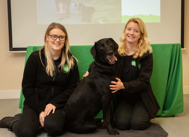 Black Labrador Fidget sitting with Emmi and Robbie from our Family Dog Team