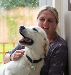 Volunteer at her home stroking yellow Labrador puppy