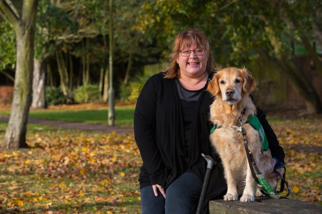 Vicki sitting with her assistance dog Tula a golden retriever in the park