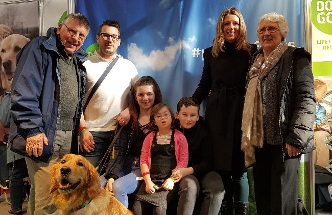 Milli with assistance dog Emma and her family on our stand at Crufts